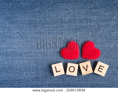 Word spell love and red heart shape on blue jean background