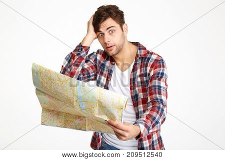 Portrait of a bewildered young man holding travel map and looking at camera isolated over white background