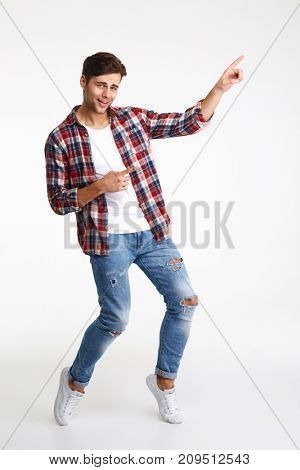 Full length portrait of a young smiling man pointing two fingers away at copy space isolated over white background