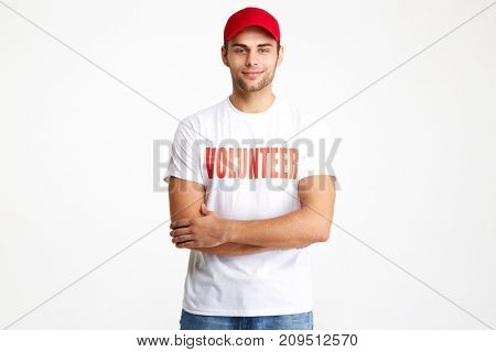 Portrait of a confident smiling man wearing volunteer t-shirt standing with arms folded and looking at camera isolated over white background