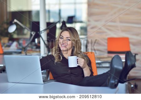 Happy beautiful young business woman sitting and talking on cell phone in office.