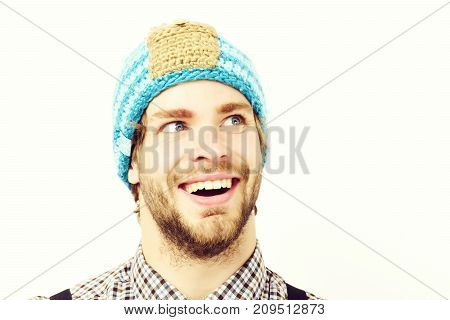 Man in winter hat and plaid shirt isolated on white background. Guy with funny hat in blue beige and orange color. Bearded man with happy face wears hat. Winter and casual style clothes concept