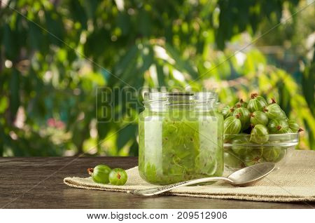 Gooseberry smoothie in a jar on a brown table and background of green leaves