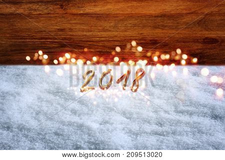 New year background with snow and bokeh in front of a rustic wooden wall for a congratulations card