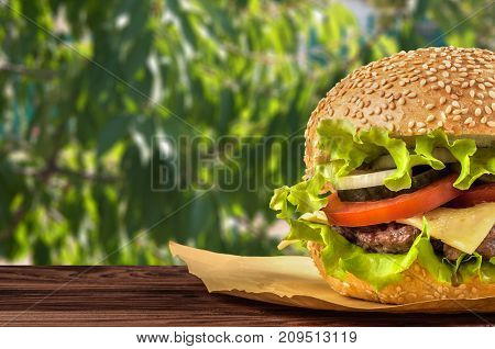 Delicious cheeseburger with salad ingredients on a grilled beef patty on a rustic wooden table with copyspace.
