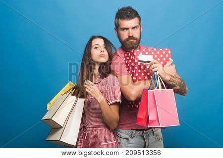 Couple In Love Stands Back To Back Holding Shopping Bags