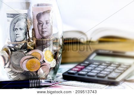 US dollar bill versus China yuan bill and coins in a glass jar on the table. The concept of business growth financial or money savings
