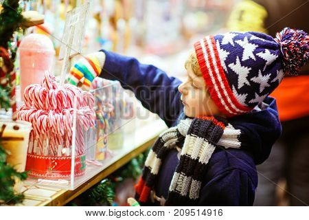 Little cute kid boy buying sweets from a cancy stand on Christmas market. Happy child on traditional family market in Germany. Preschooler in colorful winter clothes.