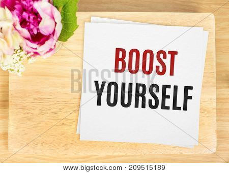 Top View Of Boost Yourself Word On White Paper On Wood Table With Flower,motivate Quote