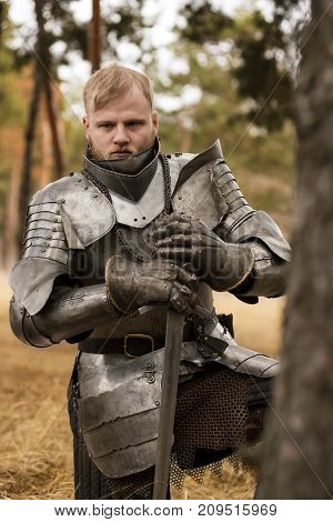Knight In Armour Before Battle On Forest Background