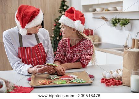 Cheerful grandmother and girl are celebrating Christmas together. They are standing in kitchen and smiling. Senior lady is holding colorful cookie