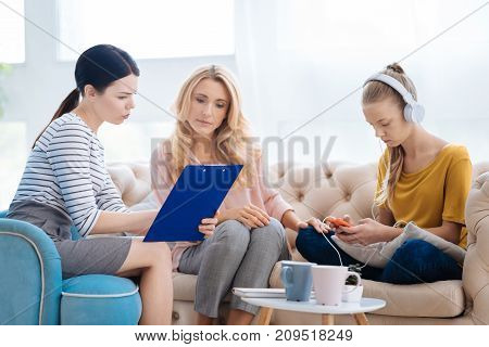 Psychological help. Intelligent smart professional therapist holding notes with the diagnosis and talking to her patients mother while explaining the diagnosis