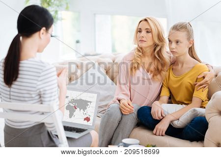 What do you see. Pleasant nice caring woman hugging her daughter and talking to her while visiting a psychologist