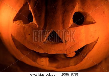 Funny orange pumpkin like a head with carved eyes and a smile on a black background with a garland for the Halloween party