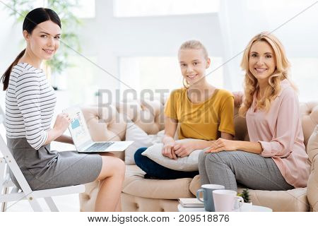 Helpful therapy. Nice positive cheerful people sitting together and smiling while looking at you