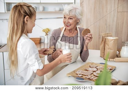 Lets try our masterpiece. Joyful grandmother and girl are tasting self-made cookies with milk. They are looking at each other and smiling