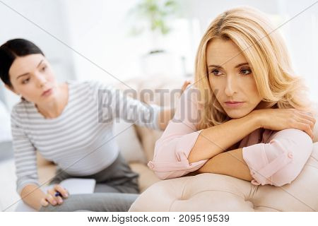 Difficult times. Depressed cheerless unhappy woman visiting a therapist and sitting on the sofa while thinking about her problems