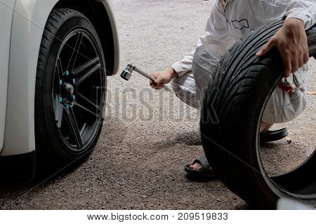 Hands of mechanic in white uniform holding wrench at the repair garage background. Car service concept.
