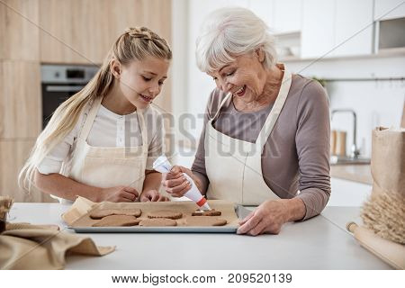 Joyful grandmother and granddaughter are making Christmas cookies. Senior woman is decorating pastry by cream and laughing