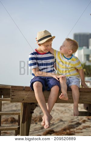 Cute kid boy and little toddler sitting on the wooden pier and enjoying summer day on the beach. Boys with bare feet. Vacation by the sea. Outdoors. Siblings. Brothers by the ocean.