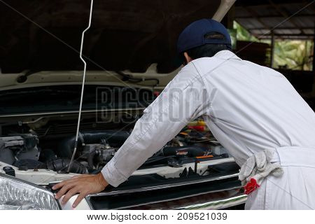 Side view of automotive mechanic in white uniform diagnosing engine under hood of car at the repair garage.