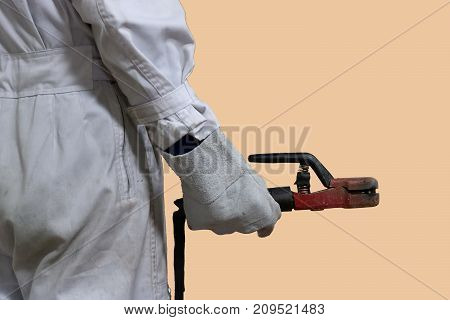 Back view of professional welder worker in white uniform holding arc welding torch in his hands on isolated background.