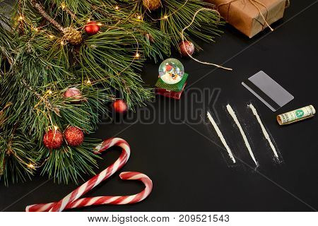 Cocaine divided into paths with Xmas toys and spruce branch on black background top view. Copy space. Still life. Flat lay. New year