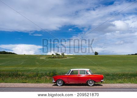 Retro car. The red-and-white car. In the field.