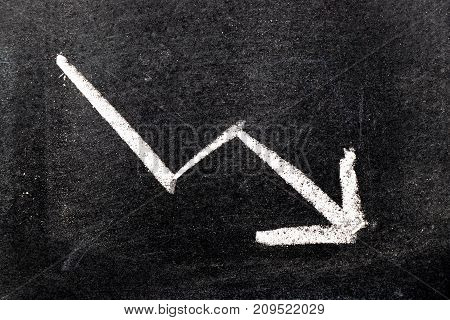White color hand drawing chalk in arrow down shape on black board background (Concept of stock decline down trend of business economy)