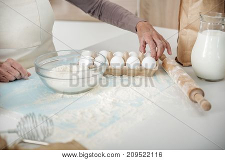 Close up of wrinkled female hand taking an egg from set. Focus on flour in bowl and rolling pin on table