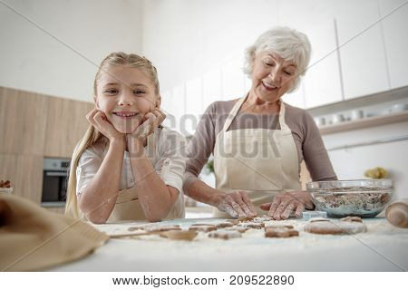 Happy childhood. Low angle of pretty girl enjoying baking process with her grandmother. They are standing at table and laughing