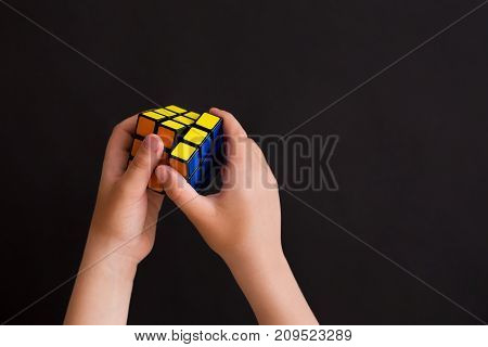 Moscow Russia August 24 2017: Rubik's cube in child's hands closeup black background. Boy holding Rubik's cube and playing with it.