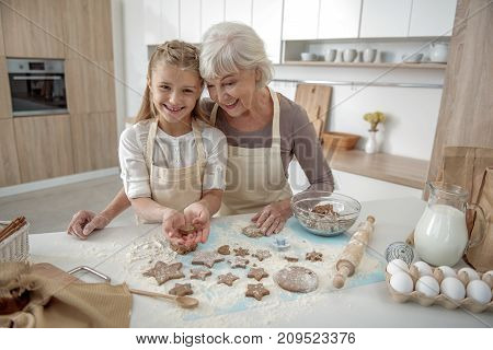 Waist up portrait of cheerful girl presenting self-made shape of dough to her grandmother. They are standing in kitchen and laughing