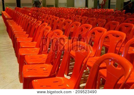 Row Of Well Organized Red Plastic Chair In The Plearnary Hall For Biggest Event.