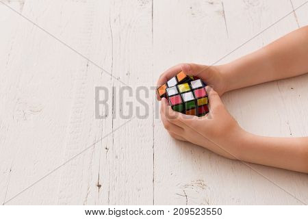 Moscow Russia August 24 2017: Rubik's cube in child's hands closeup top view white wooden background. Boy holding Rubik's cube and playing with it.