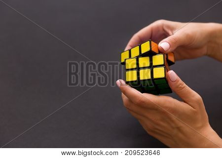 Moscow Russia August 24 2017: Rubik's cube in woman's hands closeup grey background. Girl holding Rubik's cube and playing with it.
