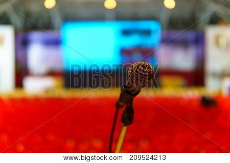 Close Up Of Microphone In The Seminar Hall For Speaker Or Singer With Blurred Row Of Red Plastic Cha