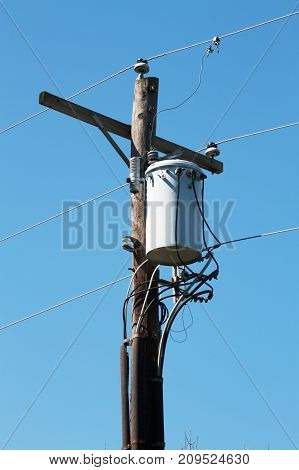 A electric power transformer pole with power lines.
