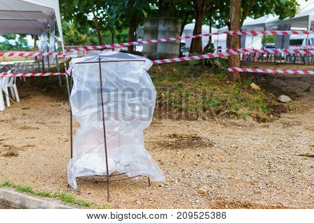 big transparent trash bag hanging on rusty steel structure for security policy to see if terrorist put bomb in it with Red and white tripped tape fence for barricades or murder zones or crime scene.