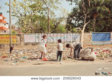 JAIPUR, INDIA - JAN 21, 2015: Poverty in action family of poor children and father looking for plastic rubbish in trash heap to earn penny on January 21, 2015. Jaipur has population 6664000 people