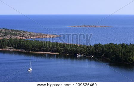 View of the archipelago in the High Coast World Heritage, Sweden. Sailboat, beach and islands. Summer and sunshine.