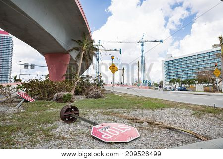 Miami Florida USA September 20 2017: Damaged trees and road sign stop on one of the streets. After hurricane Irma. Trash and damaged objects under the bridge.
