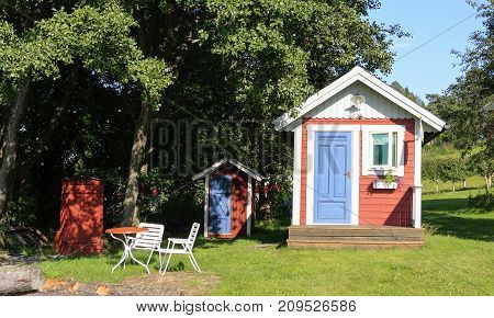 HIGH COAST WORLD HERITAGE, SWEDEN ON AUGUST 06. View of red, blue and white playhouse in a garden on August 06, 2009 in High Coast World Heritage, Sweden. Editorial use.