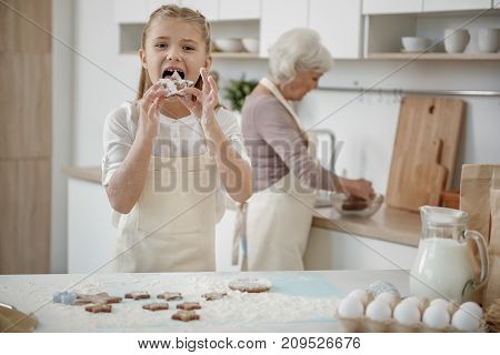Portrait of hungry girl eating self-made cookie while standing near table with flour on it. Her granny is preparing dough on background