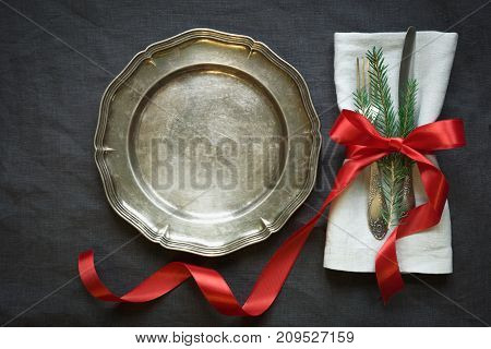 Christmas table setting with vintage dishware, silverware and decorations on gray linen tablecloth. Top view.