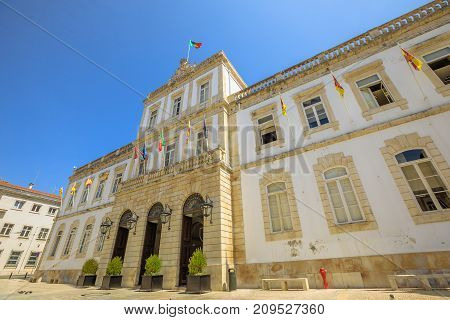 Facade of Town Hall of historic center of Coimbra in Praca 8 de Maio, sunny day with blue sky. Coimbra University Town in Central Portugal, Europe. Bottom view.