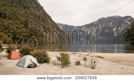 Two tents in a campsite near a lagoon in the mountain / Camping gear / Camping on the beach next to a lake with cloudy sky