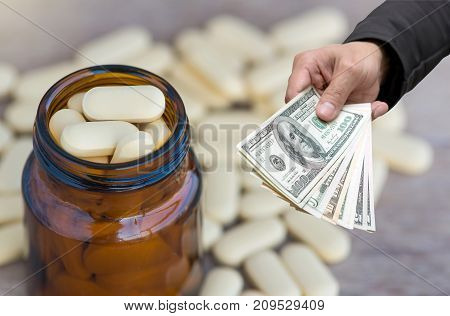 Businessman Hand with usd dollar money for Pills or vitamin in Medicine bottles on wood background