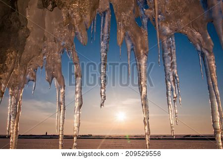 Ice with icicle, sky, sun and snow background. Lake Baikal. Russia