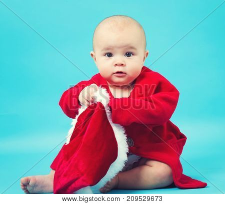 Baby girl in a Santa costume on a blue background